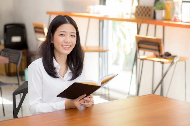 Piękny portret biznesowy azjatykci kobiety czytanie na notatniku z sukcesem