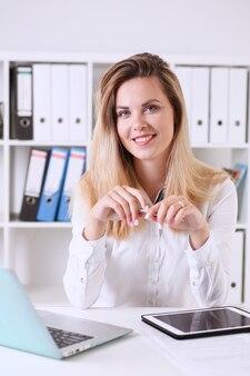 Piękny portret bizneswoman w biurze siedzi przy stole, uśmiechając się i patrząc bezpośrednio