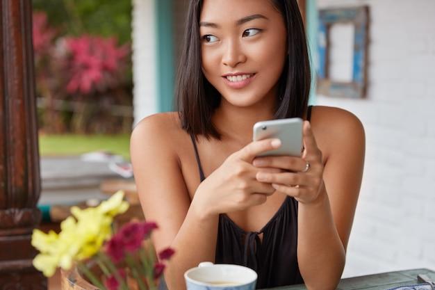 Piękny portret chinki rozmawia ze smartfonem w kawiarni