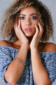 Piękny portret czarnej kobiety. testuje emocje oszołomienia strachem przed terrorem zamieszanie uroda moda styl kręcone włosy z białymi oczkami blokującymi widok