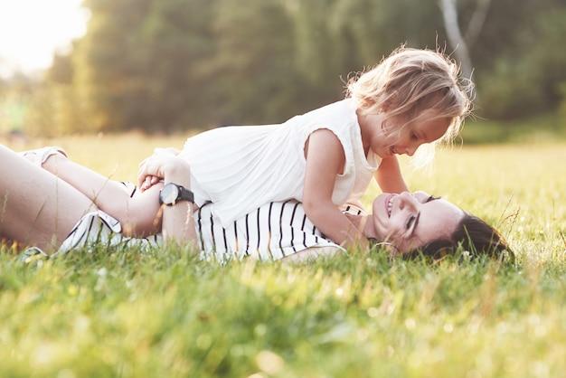 Piękny portret dziewczyny i jej córki przytulają się na zewnątrz