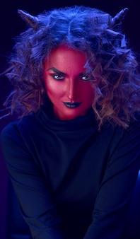 Piękny portret dziewczyny wampir z czerwoną skórą i rogami na głowie, jasne oczy z czarnymi ustami