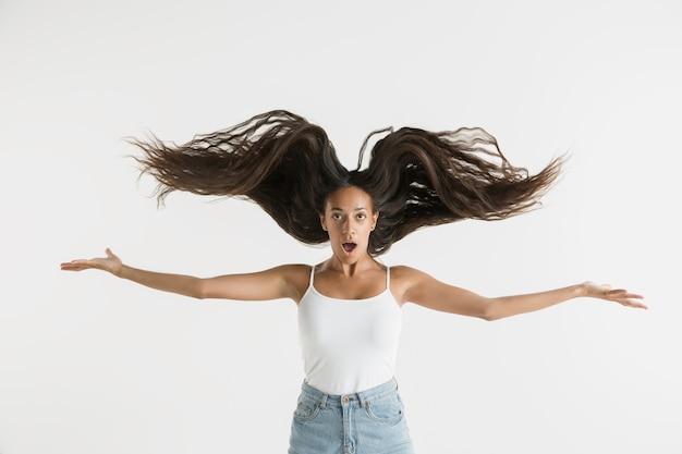 Piękny portret kobiety na białym tle. młoda emocjonalna afroamerykańska kobieta z długimi włosami. wyraz twarzy, koncepcja ludzkich emocji. czuje się szalenie szczęśliwy, skacząc.