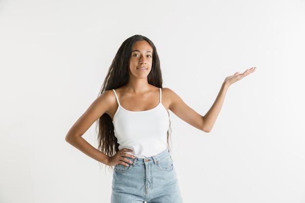 Piękny portret kobiety na białym tle. młoda emocjonalna afroamerykańska kobieta z długimi włosami. wyraz twarzy, koncepcja ludzkich emocji.