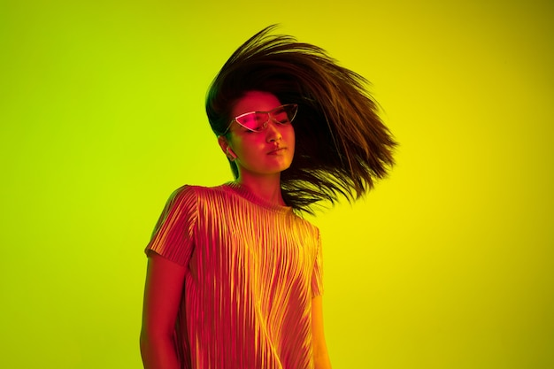 Piękny portret kobiety połowie długości na białym tle na żółtym tle studio w świetle neonowym. młoda kobieta emocjonalna. ludzkie emocje, koncepcja wyraz twarzy. tańcz w okularach i bezprzewodowych słuchawkach.