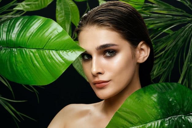 Piękny portret kobiety w krzakach palmowych, piękna skóra twarzy