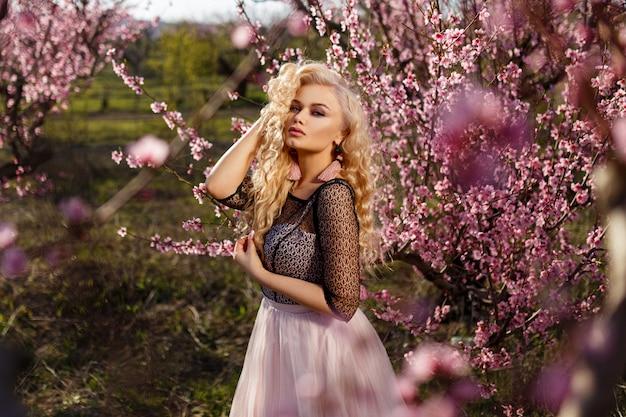 Piękny portret kobiety w ogrodzie kwitnących brzoskwiń