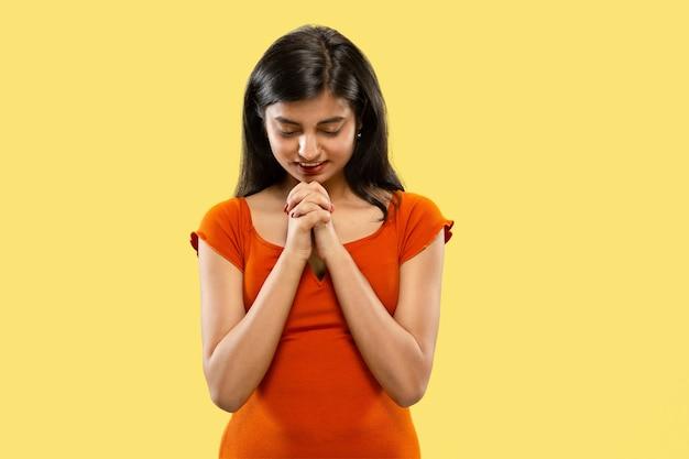 Piękny portret kobiety w połowie długości na białym tle. młoda emocjonalna indyjska kobieta w sukni modląc się lub martwiąc się. negatywna przestrzeń. wyraz twarzy, koncepcja ludzkich emocji.