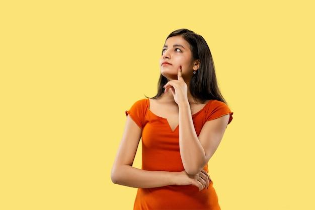 Piękny portret kobiety w połowie długości na białym tle. młoda emocjonalna indyjska kobieta w sukni myślenia poważne. negatywna przestrzeń. wyraz twarzy, koncepcja ludzkich emocji.