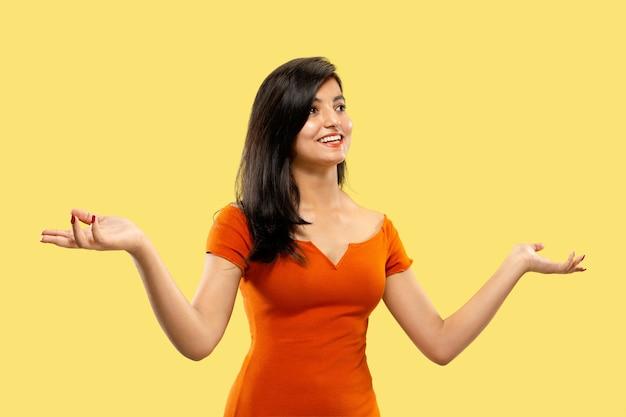 Piękny portret kobiety w połowie długości na białym tle. młoda emocjonalna indyjska kobieta w sukni, wskazując i pokazując. negatywna przestrzeń. wyraz twarzy, koncepcja ludzkich emocji.