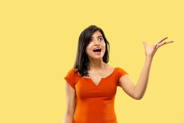 Piękny portret kobiety w połowie długości na białym tle. młoda emocjonalna indyjska kobieta w sukni zdziwiona i szczęśliwa. negatywna przestrzeń. wyraz twarzy, koncepcja ludzkich emocji.