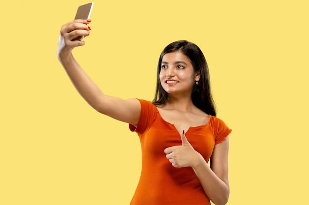 Piękny portret kobiety w połowie długości na białym tle. młoda kobieta indian emocjonalne w sukience dokonywanie selfie. negatywna przestrzeń. wyraz twarzy, koncepcja ludzkich emocji.