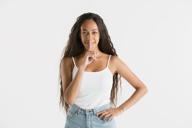 Piękny portret kobiety w połowie długości na białym tle na białej ścianie. młoda emocjonalna afroamerykańska kobieta z długimi włosami. wyraz twarzy, koncepcja ludzkich emocji. szepcząc sekret.