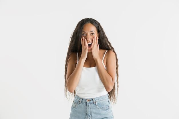 Piękny portret kobiety w połowie długości na białym tle na białej ścianie. młoda emocjonalna afroamerykańska kobieta z długimi włosami. wyraz twarzy, koncepcja ludzkich emocji. zdziwiony, podekscytowany.