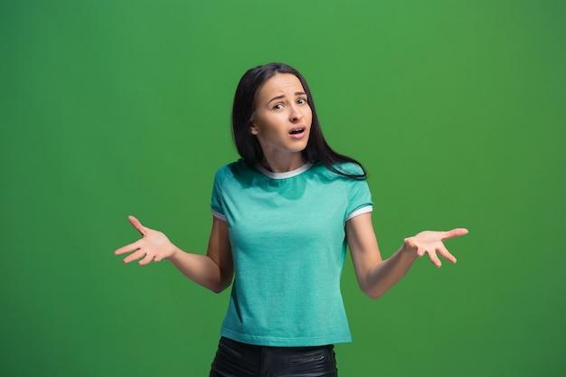Piękny portret kobiety w połowie długości na białym tle na zielonym tle studio. młody emocjonalny