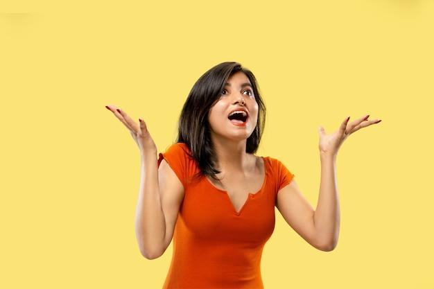 Piękny portret kobiety w połowie długości na białym tle na żółtej przestrzeni młoda emocjonalna indyjska kobieta w sukni zdziwiona i szczęśliwa. negatywna przestrzeń