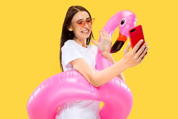 Piękny portret kobiety w połowie długości na białym tle na żółtej ścianie. młoda uśmiechnięta kobieta w czerwonych okularach przeciwsłonecznych co selfie. wyraz twarzy, lato, weekend, koncepcja ośrodka. modne kolory.