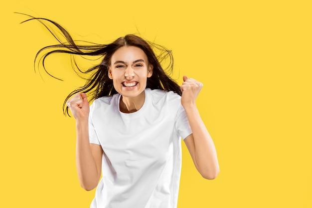 Piękny portret kobiety w połowie długości na białym tle na żółty studio