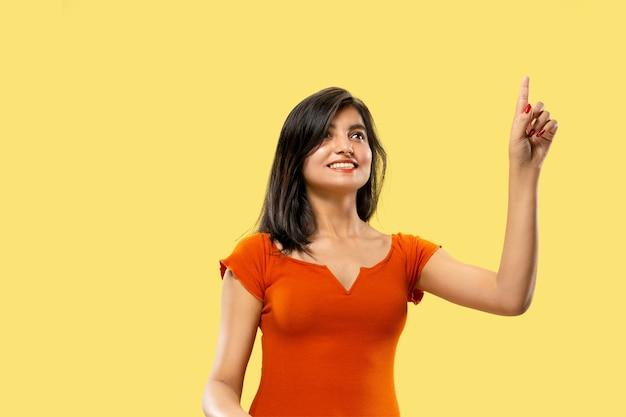 Piękny portret kobiety w połowie długości na białym tle na żółtym tle studio. młoda emocjonalna indyjska kobieta w sukni, wskazując i pokazując. negatywna przestrzeń. wyraz twarzy, koncepcja ludzkich emocji.