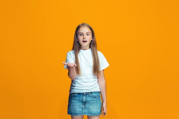 Piękny portret kobiety w połowie długości na pomarańczowym tle studio. młoda emocjonalna dziewczyna nastolatka