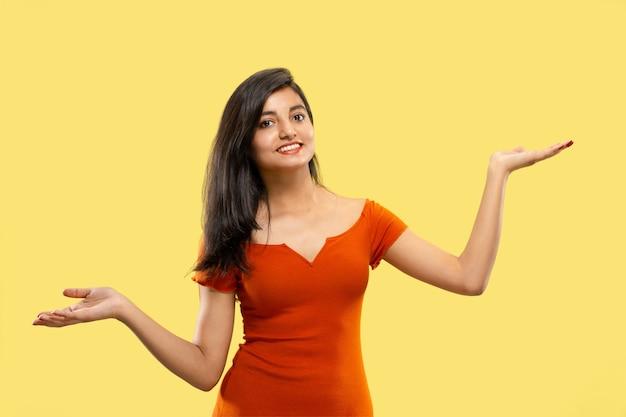 Piękny portret kobiety w połowie długości na żółtym studio