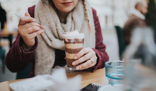 Piękny portret ładnej dziewczyny jedzącej czekoladowy deser z kubka na ulicznej kawiarni