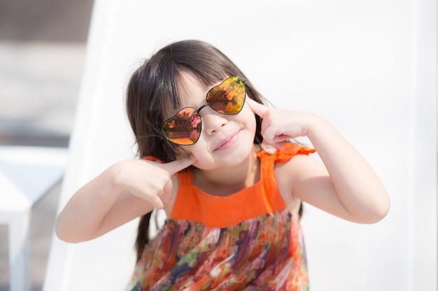 Piękny portret małej dziewczynki azjata uśmiechnięty obsiadanie przy pływackim basenem
