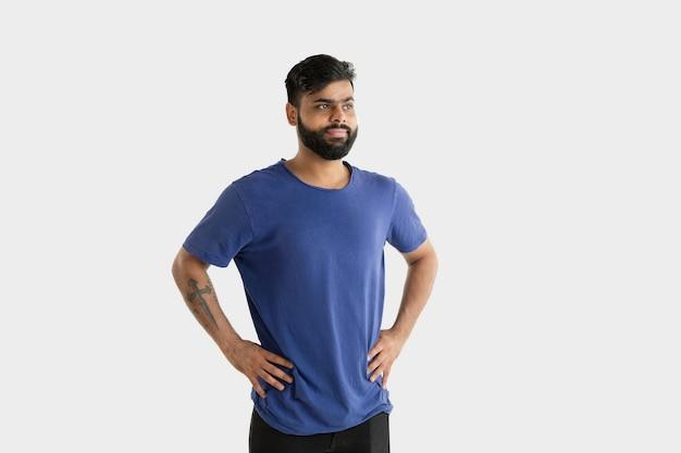 Piękny portret męski na białym tle. młody emocjonalny człowiek hinduski w niebieskiej koszuli. wyraz twarzy, ludzkie emocje. stojąc i uśmiechając się.