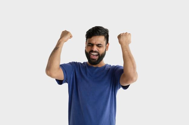 Piękny portret męski na białym tle. młody emocjonalny człowiek hinduski w niebieskiej koszuli. wyraz twarzy, ludzkie emocje. świętujemy jak zwycięzca.