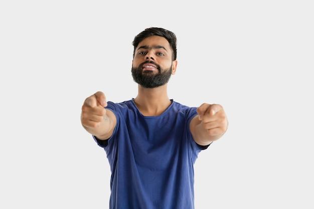 Piękny portret męski na białym tle. młody emocjonalny człowiek hinduski w niebieskiej koszuli. wyraz twarzy, ludzkie emocje. wskazywanie i wybieranie.