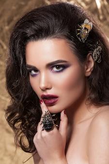 Piękny portret młodej dziewczyny, piękny makijaż, czysta skóra, fryzura, biżuteria w postaci chrząszcza i pszczoły