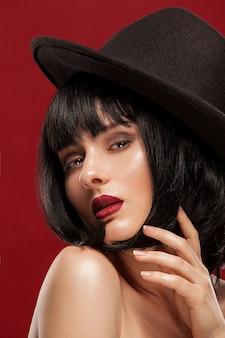 Piękny portret młodej dziewczyny. zbliżenie na czarnym tle. ciemne włosy, czarny kapelusz, profesjonalny makijaż i czysta skóra.