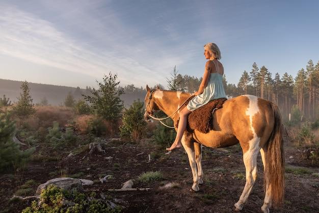 Piękny portret młodej kobiety jadącej na koniu w przepięknym krajobrazie