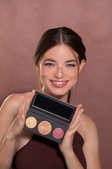 Piękny portret młodej kobiety z produktem do makijażu