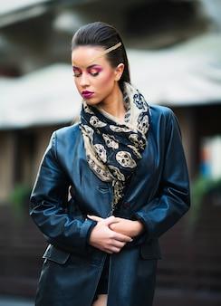 Piękny portret modelki rocka w skórzanej kurtce z ciemnym makijażem wieczorowym