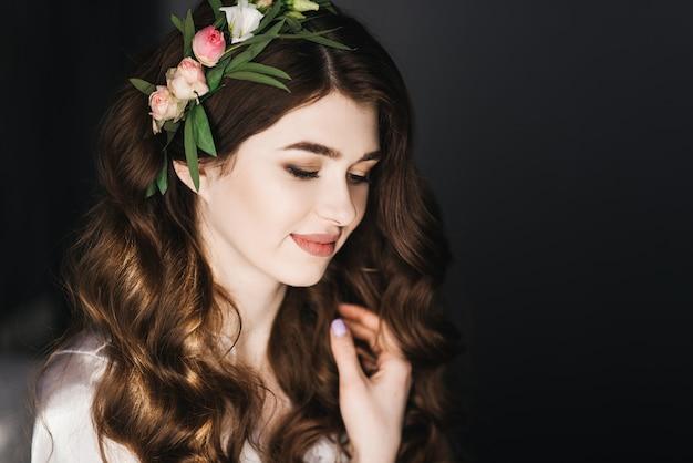 Piękny portret panny młodej z lokami i świeżymi kwiatami
