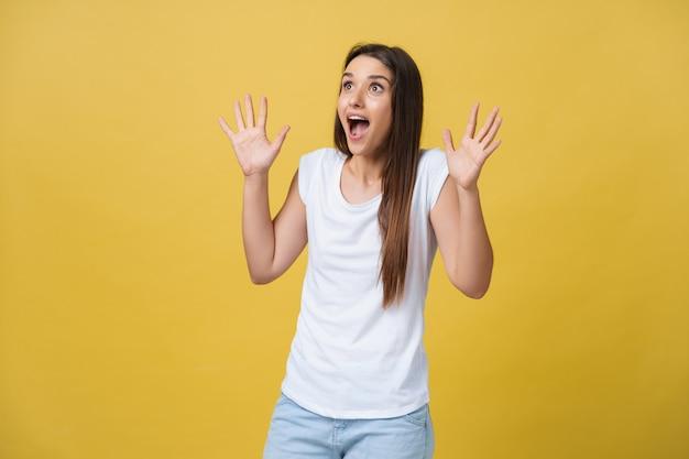 Piękny portret połowy długości kobiece kobieta na białym tle na żółtym tle studio. młoda emocjonalna uśmiechnięta i zaskoczona kobieta stojąca i patrząca na kamerę. ludzkie emocje, koncepcja wyrazu twarzy