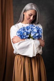 Piękny portret starszej kobiety z bukietem kwiatów