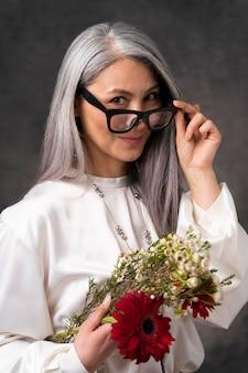 Piękny portret starszej kobiety z kwiatami