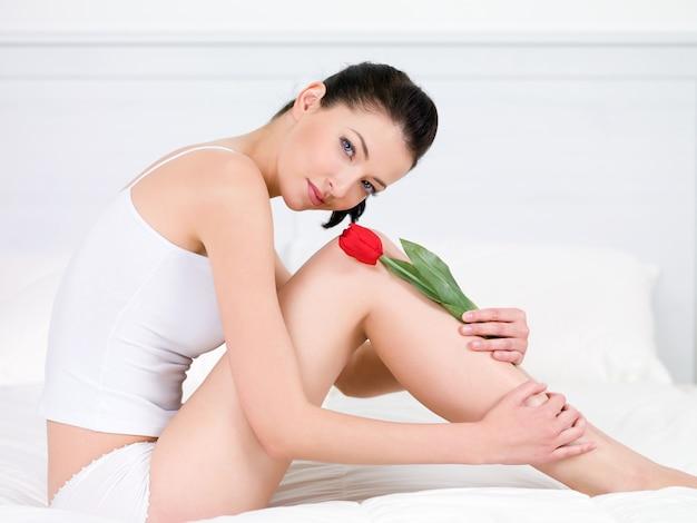 Piękny portret uśmiechnięta młoda ładna kobieta z czerwonym tulipanem na nogach - w pomieszczeniu