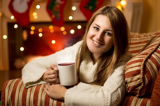 Piękny portret uśmiechniętej kobiety siedzącej z kubkiem gorącej herbaty przy kominku w wigilię bożego narodzenia