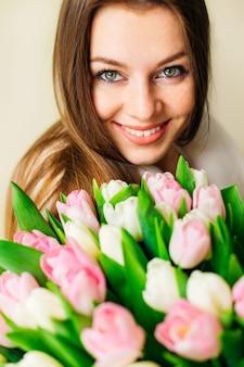 Piękny portret zbliżenie uroczej dziewczyny z dużymi zielonymi oczami lat dwudziestych uśmiechniętych i patrzących w obiektyw. dziewczyna trzyma piękny bukiet tulipanów.