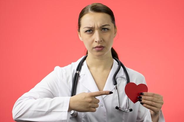 Piękny poważny kardiolog wskazując na czerwone serce, zawał serca, choroby