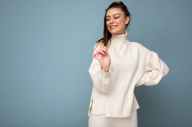 Piękny pozytywny młoda kobieta ubrana w ciepły sweter stojący na białym tle na niebieskim tle, pozowanie.