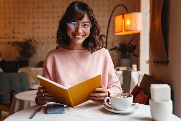 Piękny pozytywny uśmiechający się brunetka młoda kobieta pomieszczeniu w kawiarni czytanie książki.