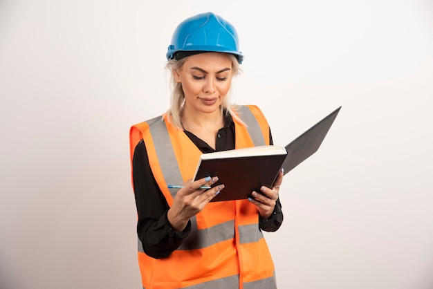 Piękny pracownik budowlany sprawdzanie notatek na białym tle. wysokiej jakości zdjęcie