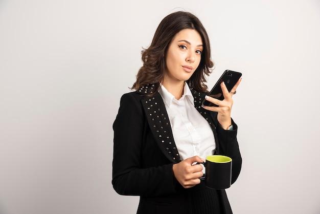 Piękny pracownik trzymający filiżankę herbaty i telefon