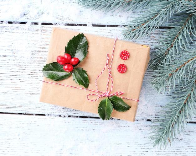 Piękny prezent cristmas z ostrokrzewem europejskim (ilex aquifolium) na drewnianym tle