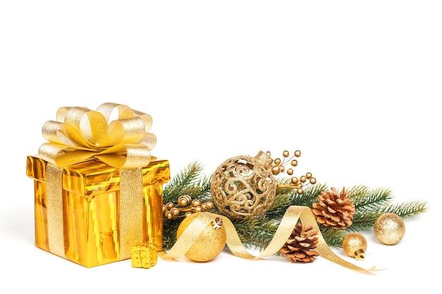 Piękny prezent w złotym opakowaniu i świąteczne dekoracje na białym tle