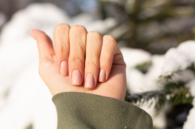 Piękny, profesjonalny manicure beżowy nude na kobiecej dłoni na tle pokrytego śniegiem drzewa w słoneczny dzień w naturalnym świetle